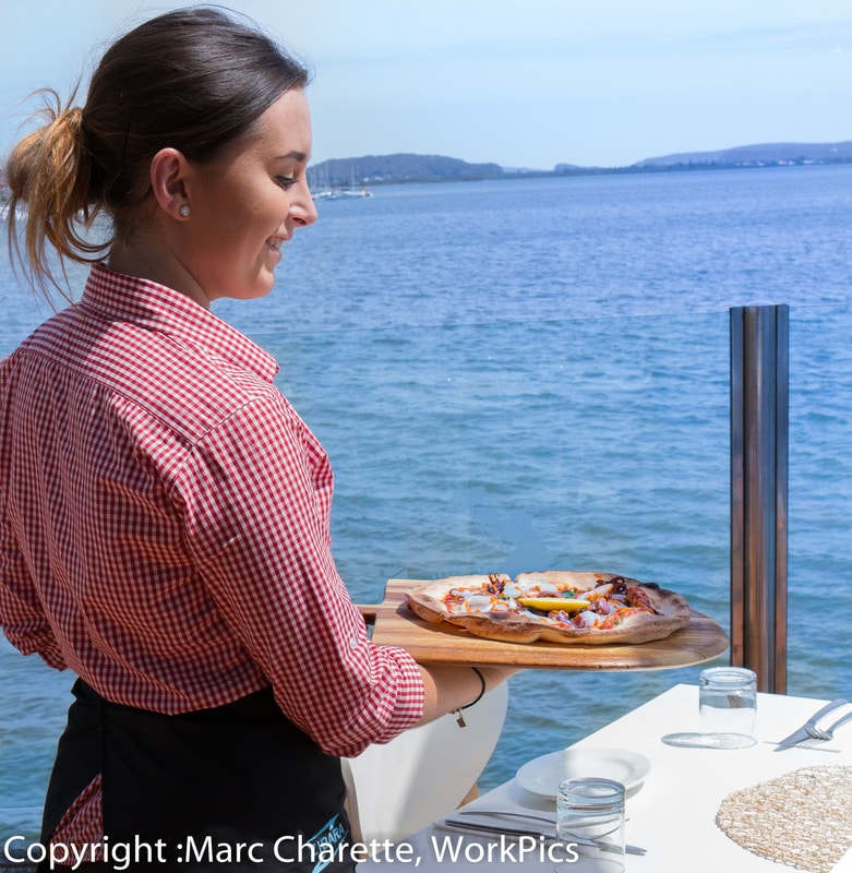 Commercial food photography of meal being served with water views
